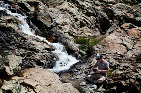 Sam stocks up on water at the last stream we saw before heading up to the impassable summit. This river cut right through the rocky slopes that it scrambled down. It was a perfect high alpine stream. (Chris Jordan-Bloch / Earthjustice)